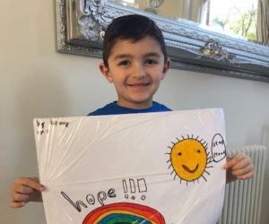 Art Gallery entry - young boy holding a sheet with a smiley sun saying 'Stay home