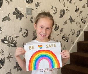 Art Gallery entry - young girl holding a sheet that says Be Safe and has a rainbow and rainbow heart