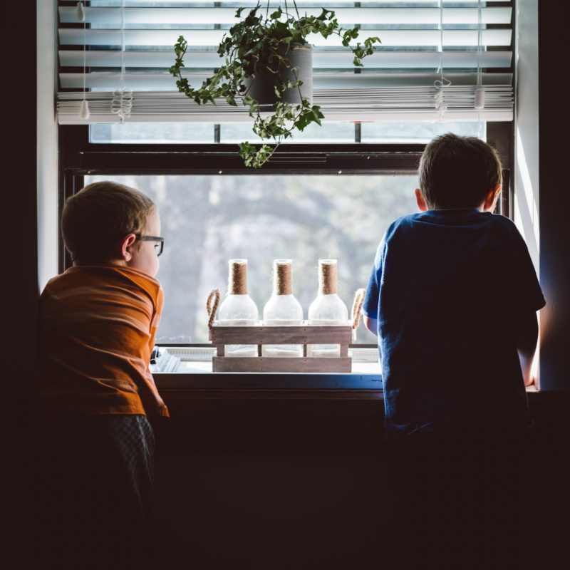 Two boys looking out of a window