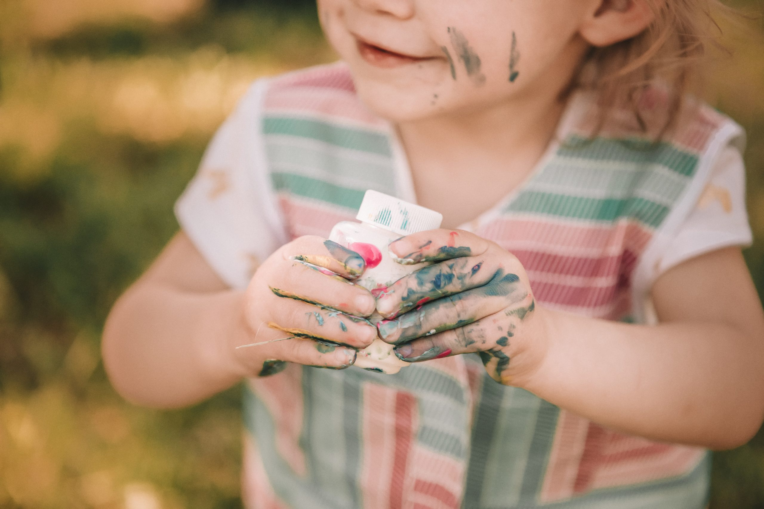 Toddler with paint all over hands