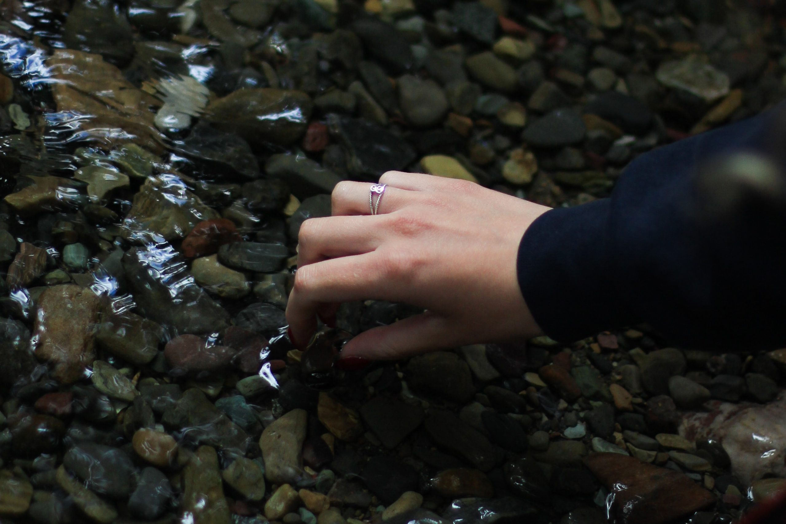 Someone picking up a pebble in a stream