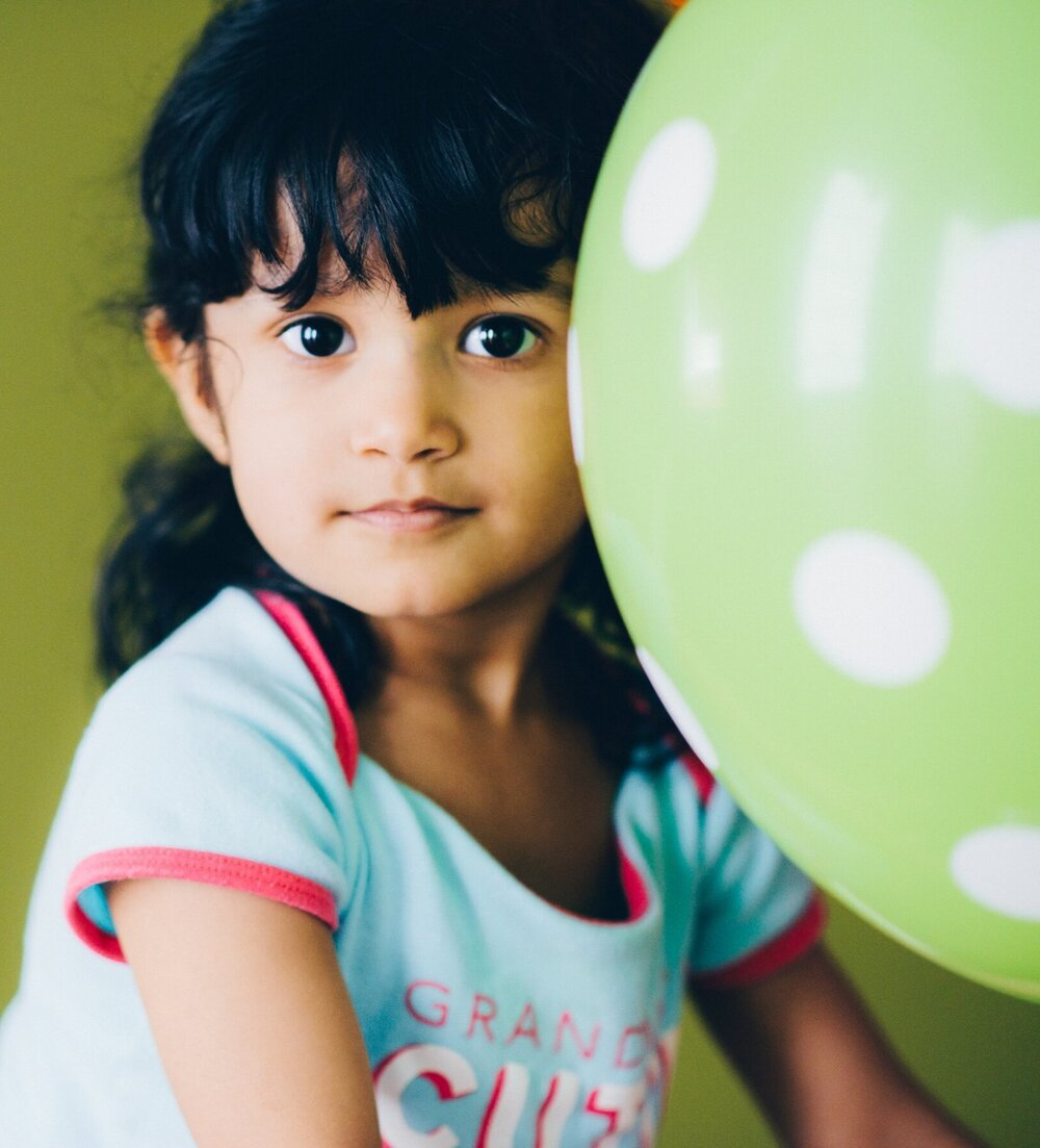 A child sits next to a green spotted balloon