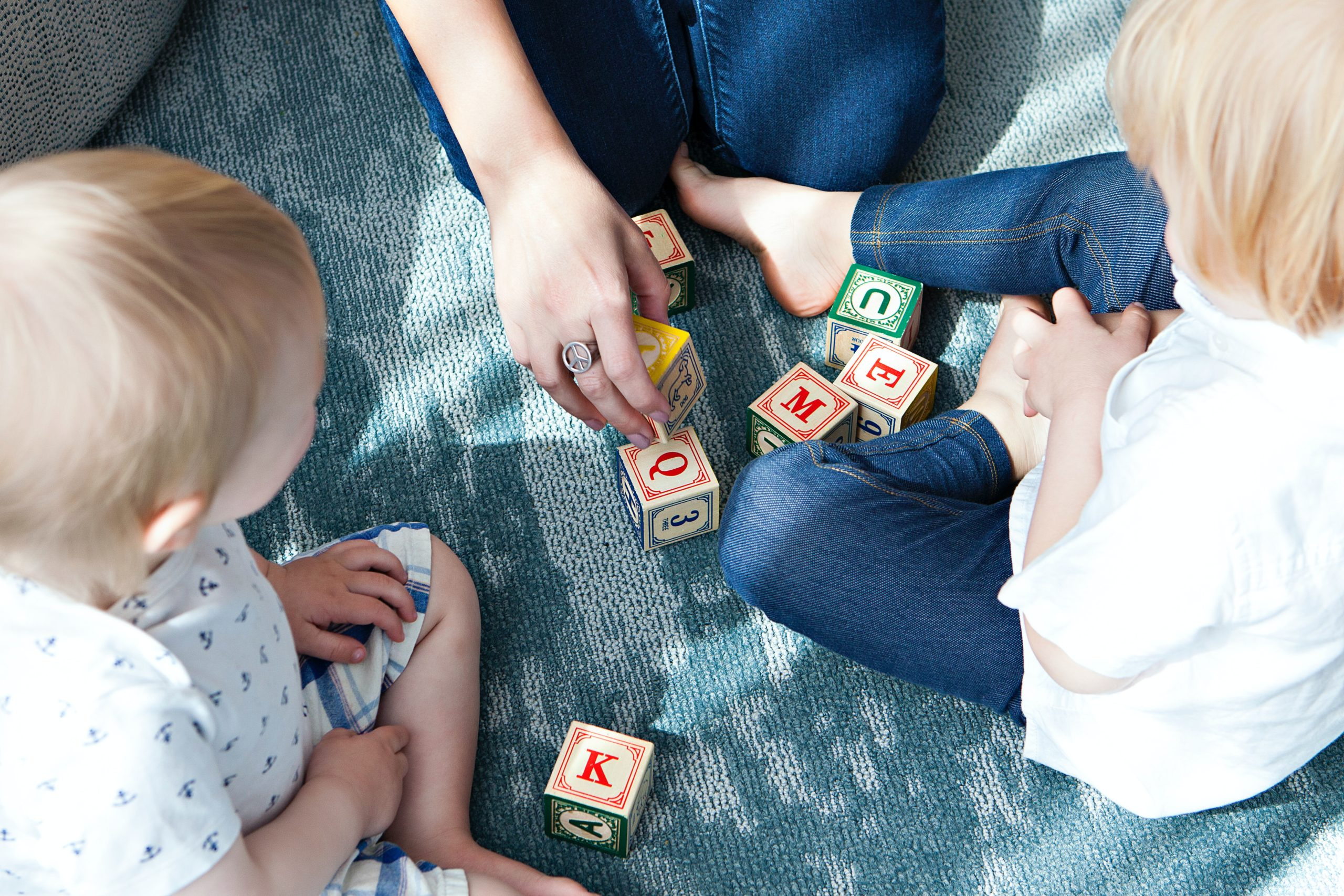 Mother playing with blocks with her two kids