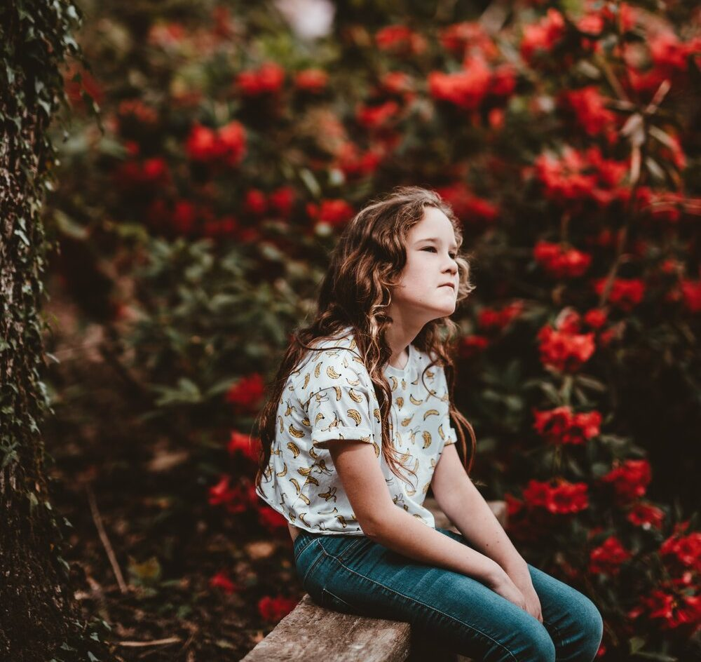little girl sitting on a bench with red flowers behind her
