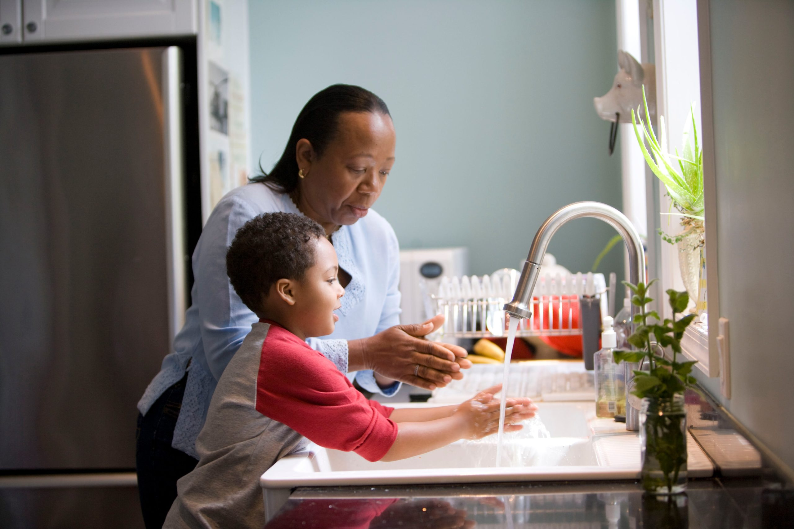 Mother teaching boy how to wash hands properly