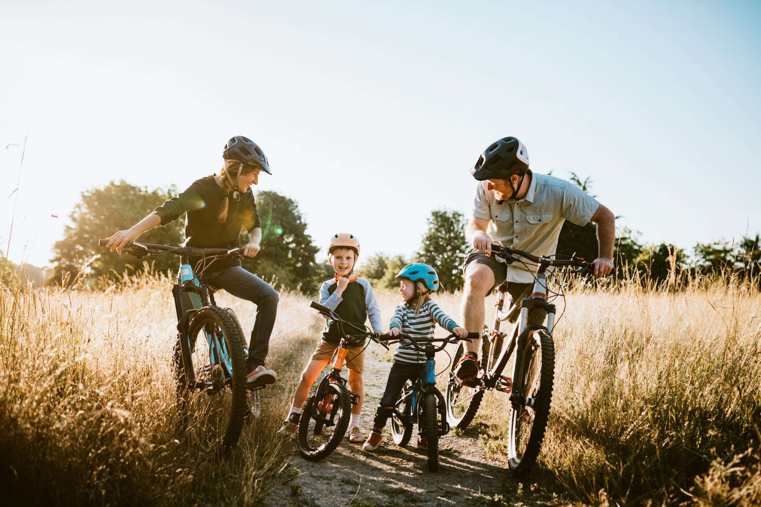 A family - mum, dad, and two kids mountain bike riding together on sunny day