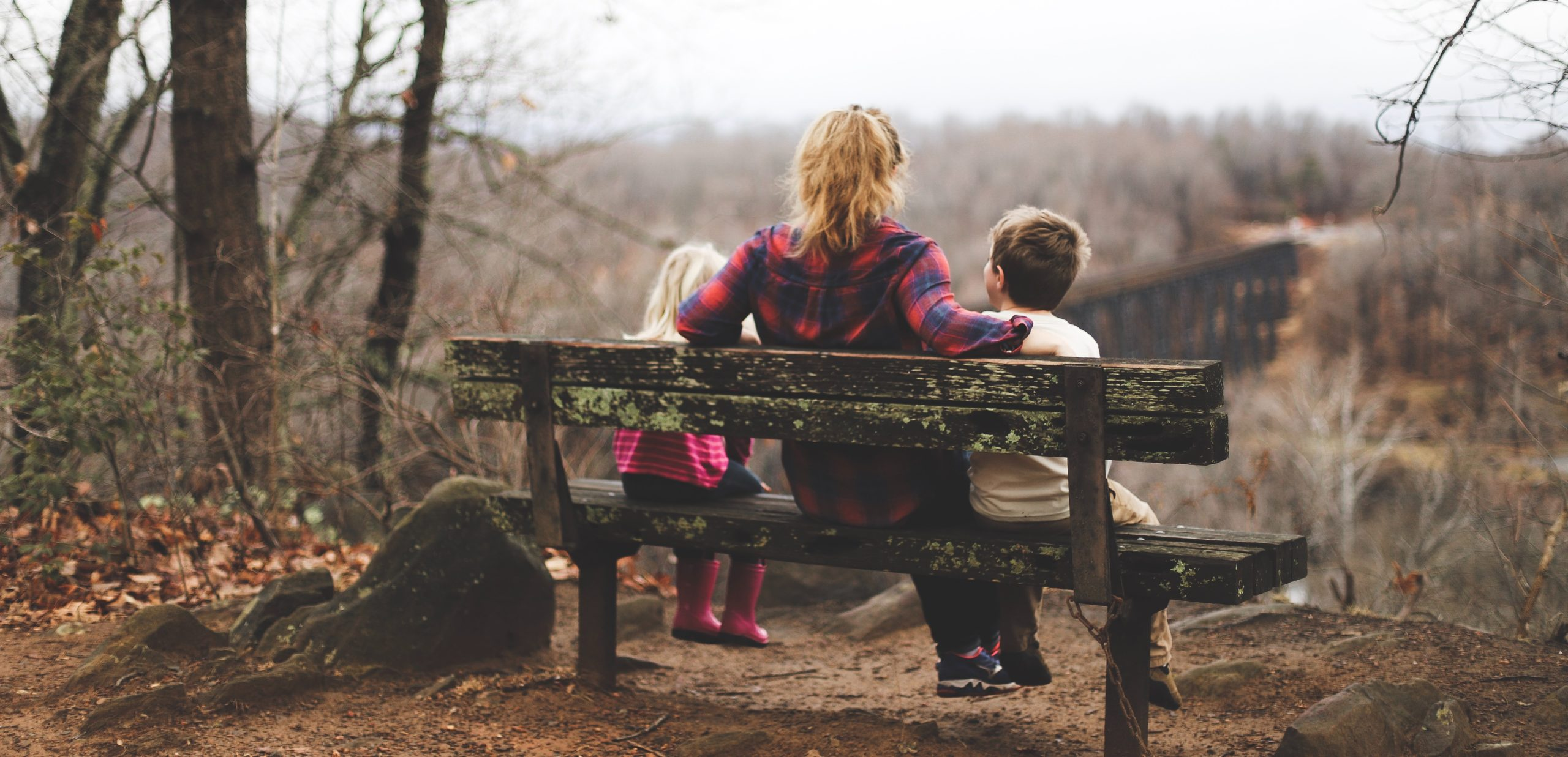 A mother and her two kids sitting on a bench looking out into a valley