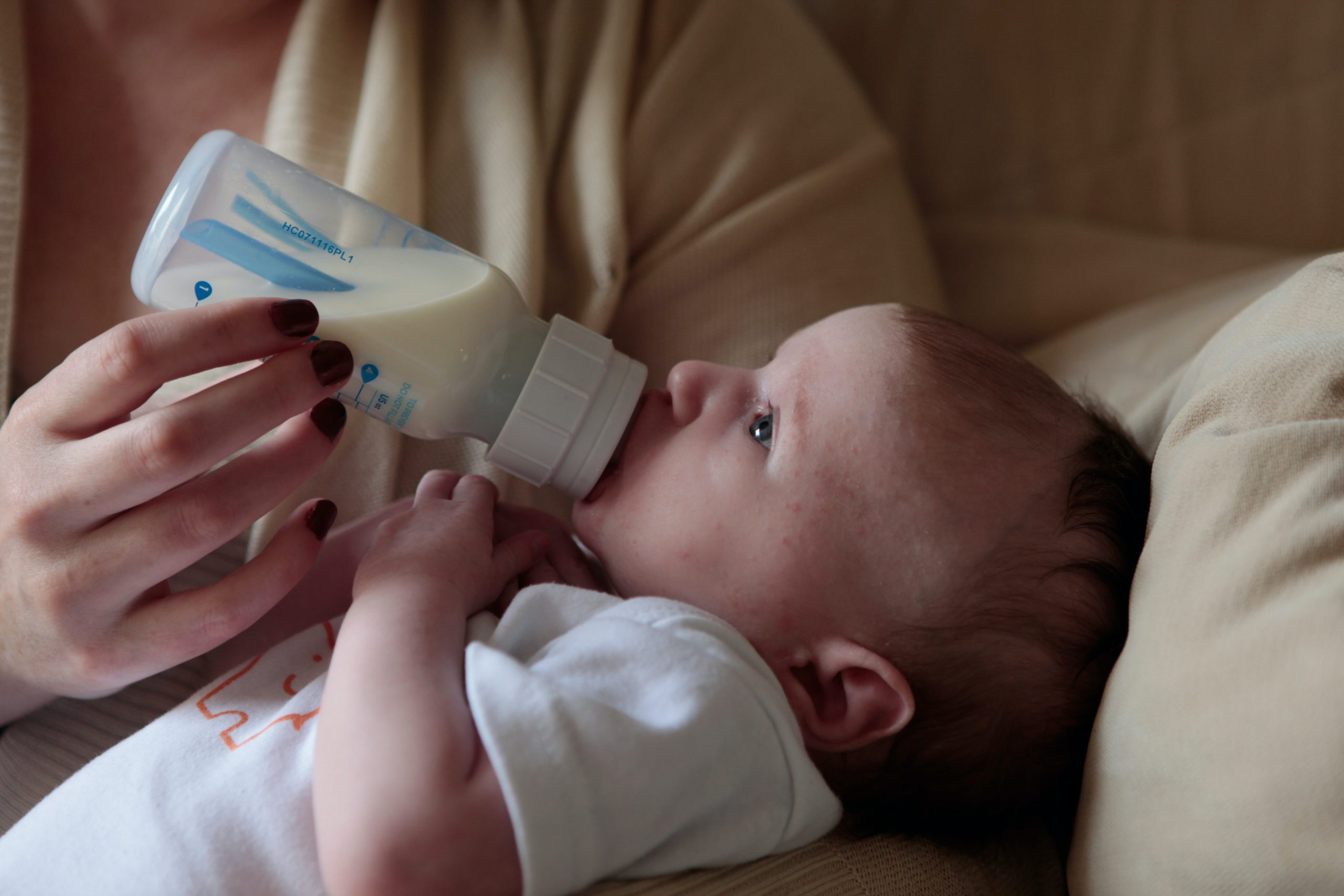 Baby being fed with milk bottle
