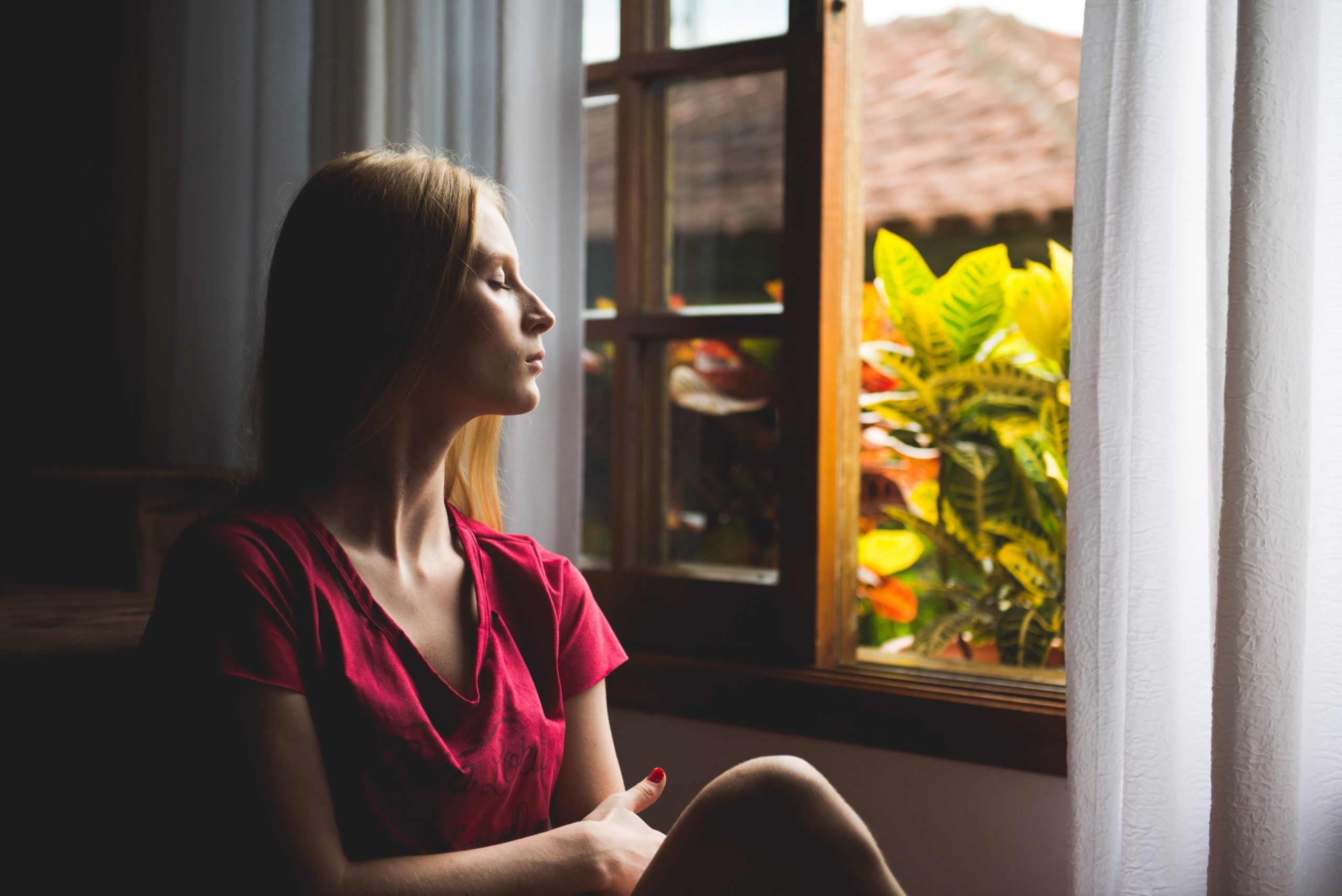 Woman sitting calmly with eyes shut near open window