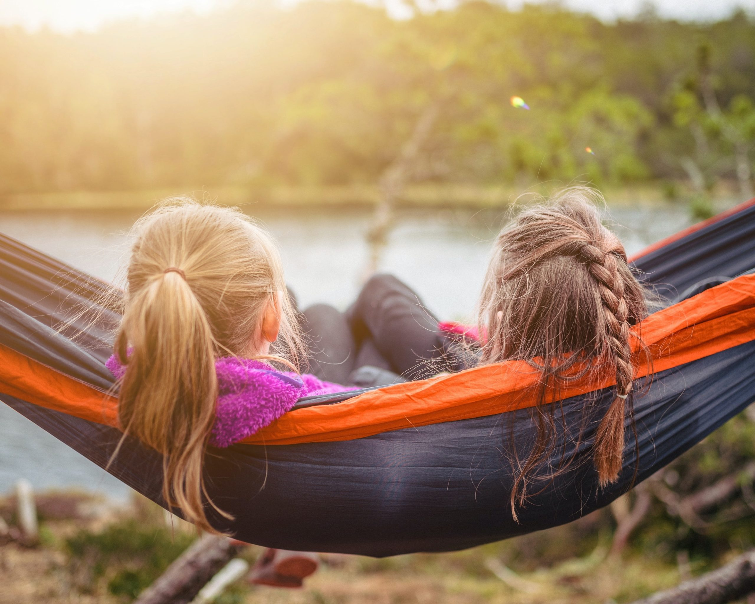 Two young girls on a hammock looking at a lake