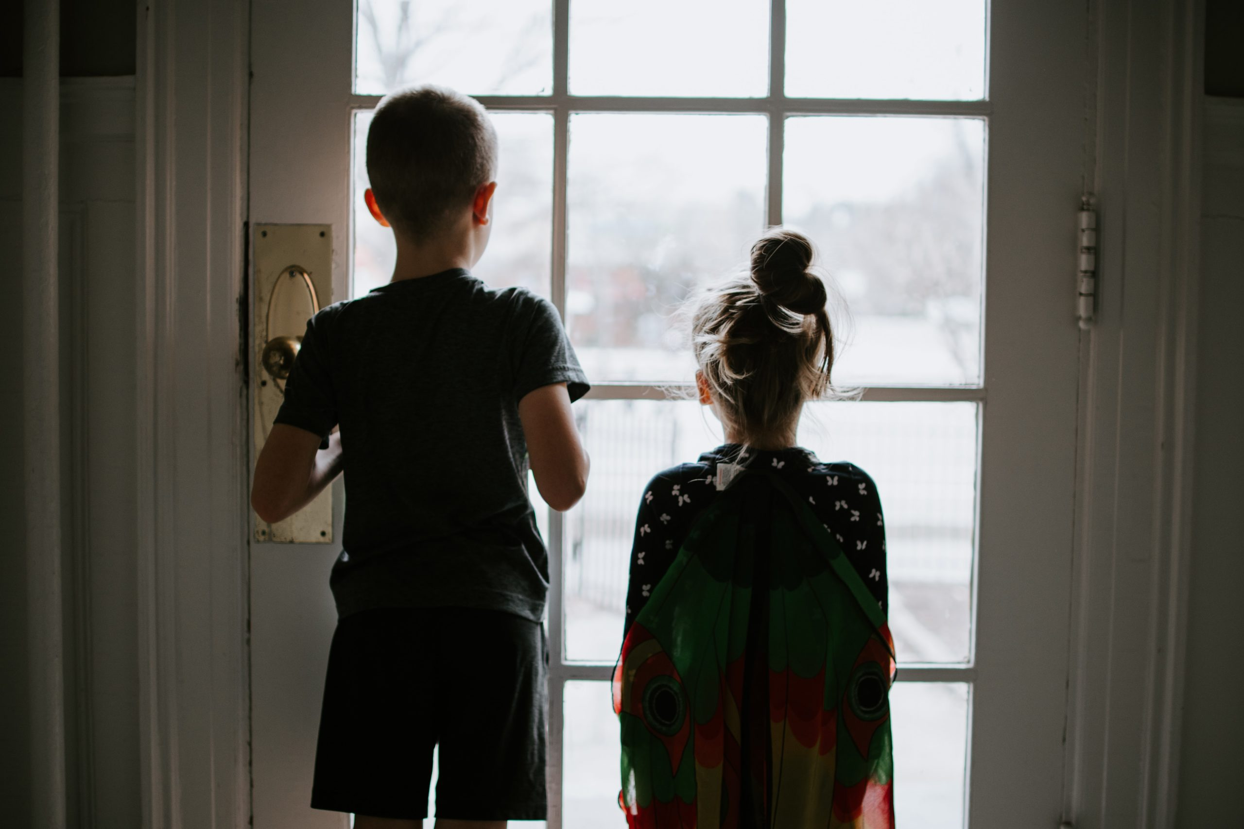 two kids looking out of door window