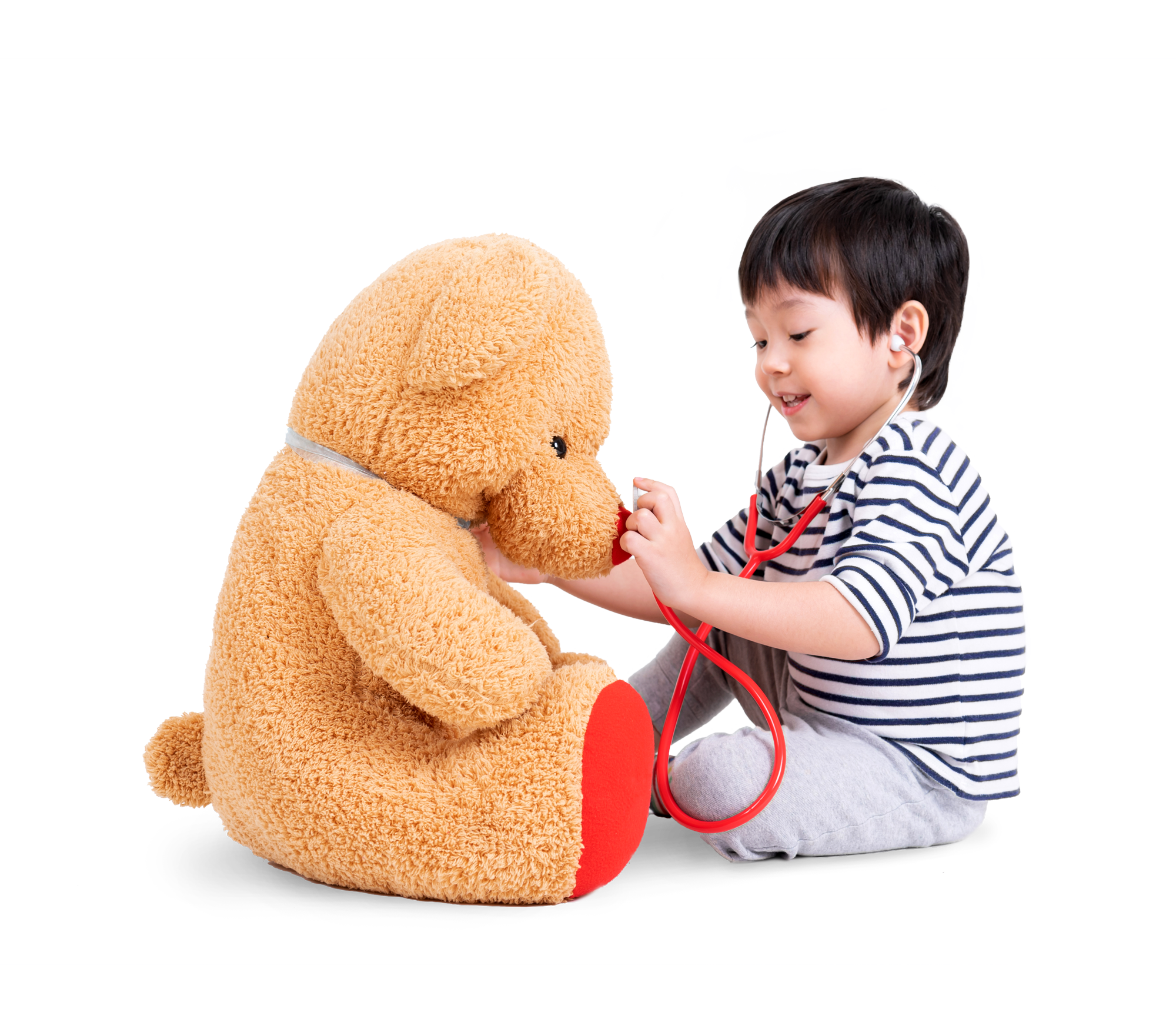 Toddler playing doctors with a teddy bear