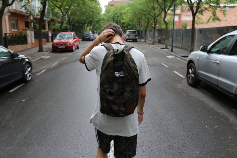 teenager walking down a road