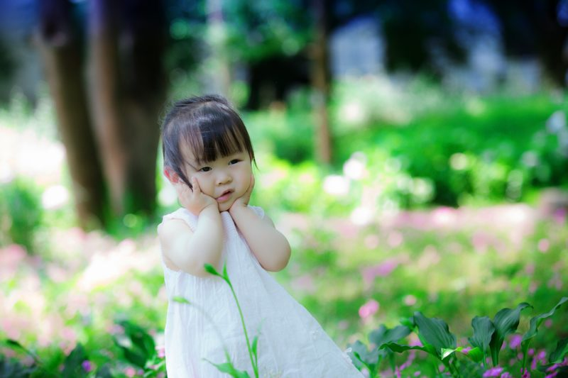 A toddler in a white dress walks through a garden with their hands on their cheeks.