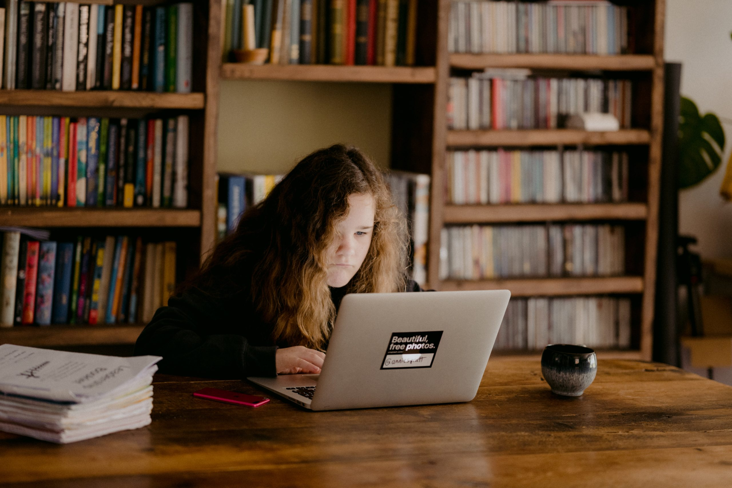 A teenager works on a laptop in front of bookshelves