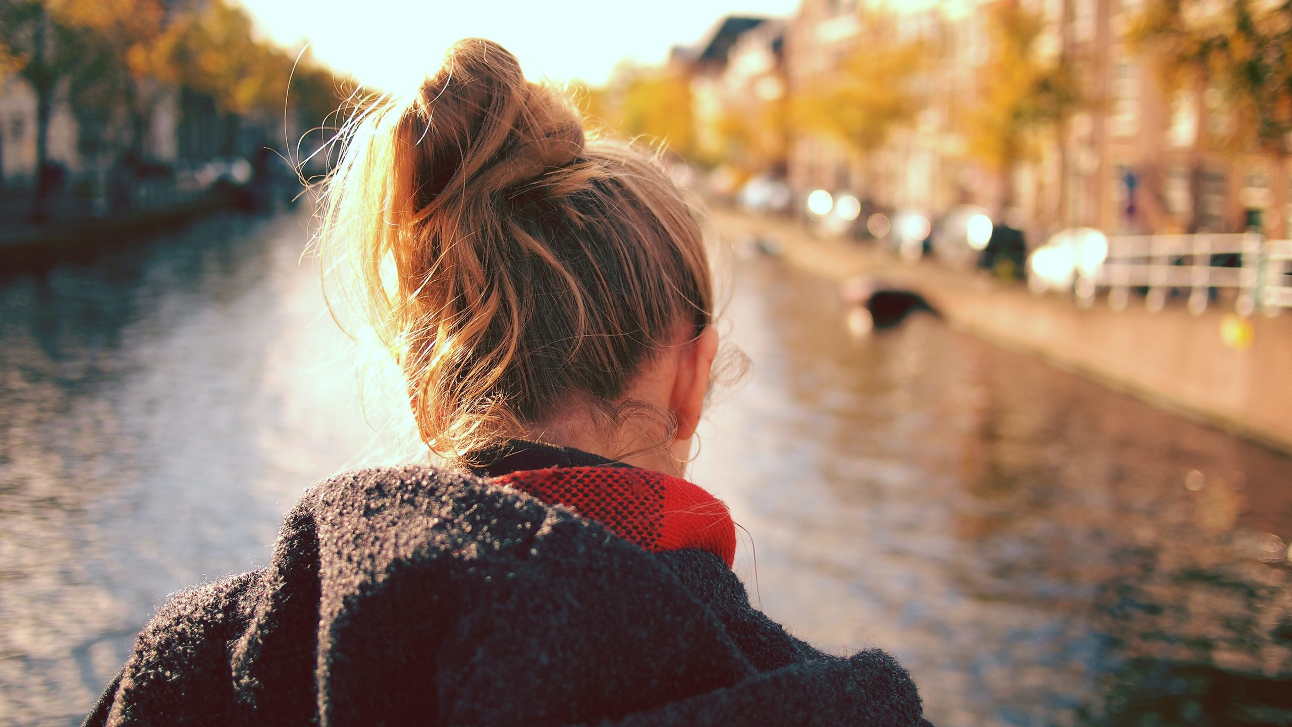 the back of a teenager's head as they face a sunlit river with their hair in a messy bun