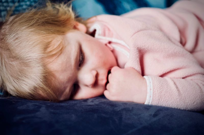 Bedtime: a child asleep with their hand by their mouth