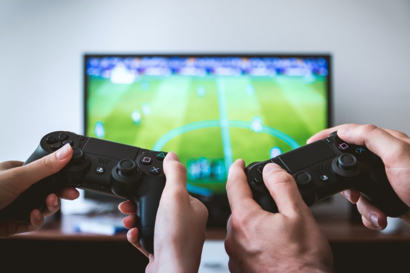 age restrictions: two people playing a video game. Only their hands are visible, holding onto consoles. There is a TV with a football pitch on in the background.