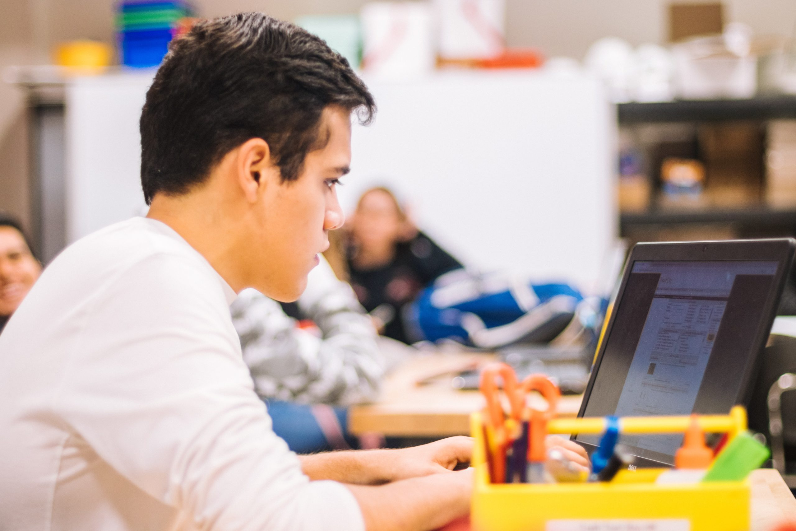 a teenager sits at a computer in school