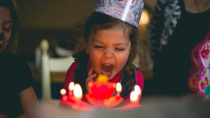 a young girl in a party hat blows out the candles on a birthday cake