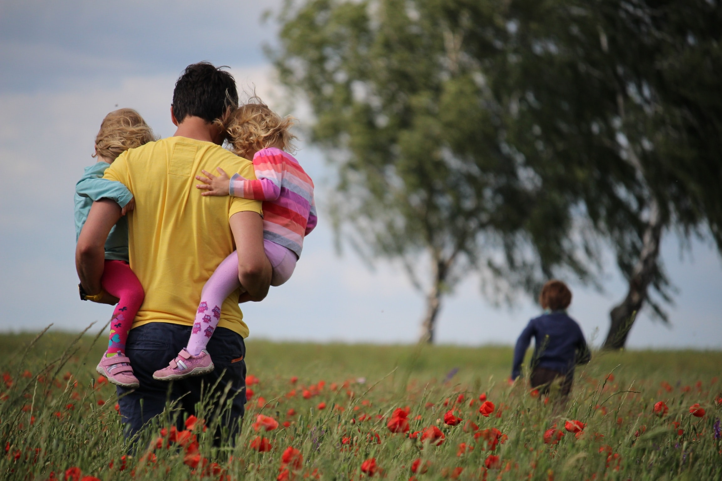 A parent walks through a poppy field holding two children. A third child is running ahead of them.