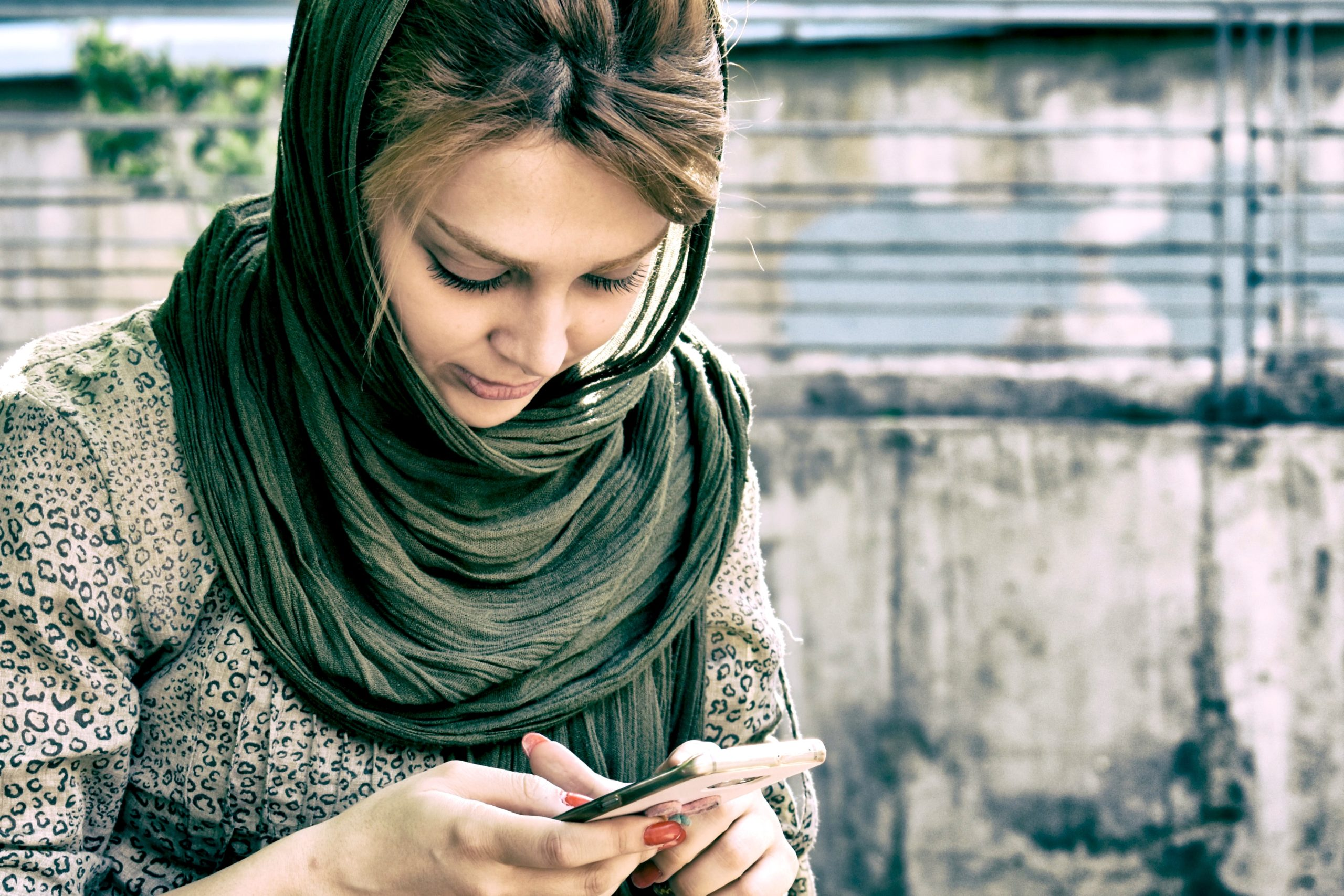 a young person in a headscarf looks at their phone