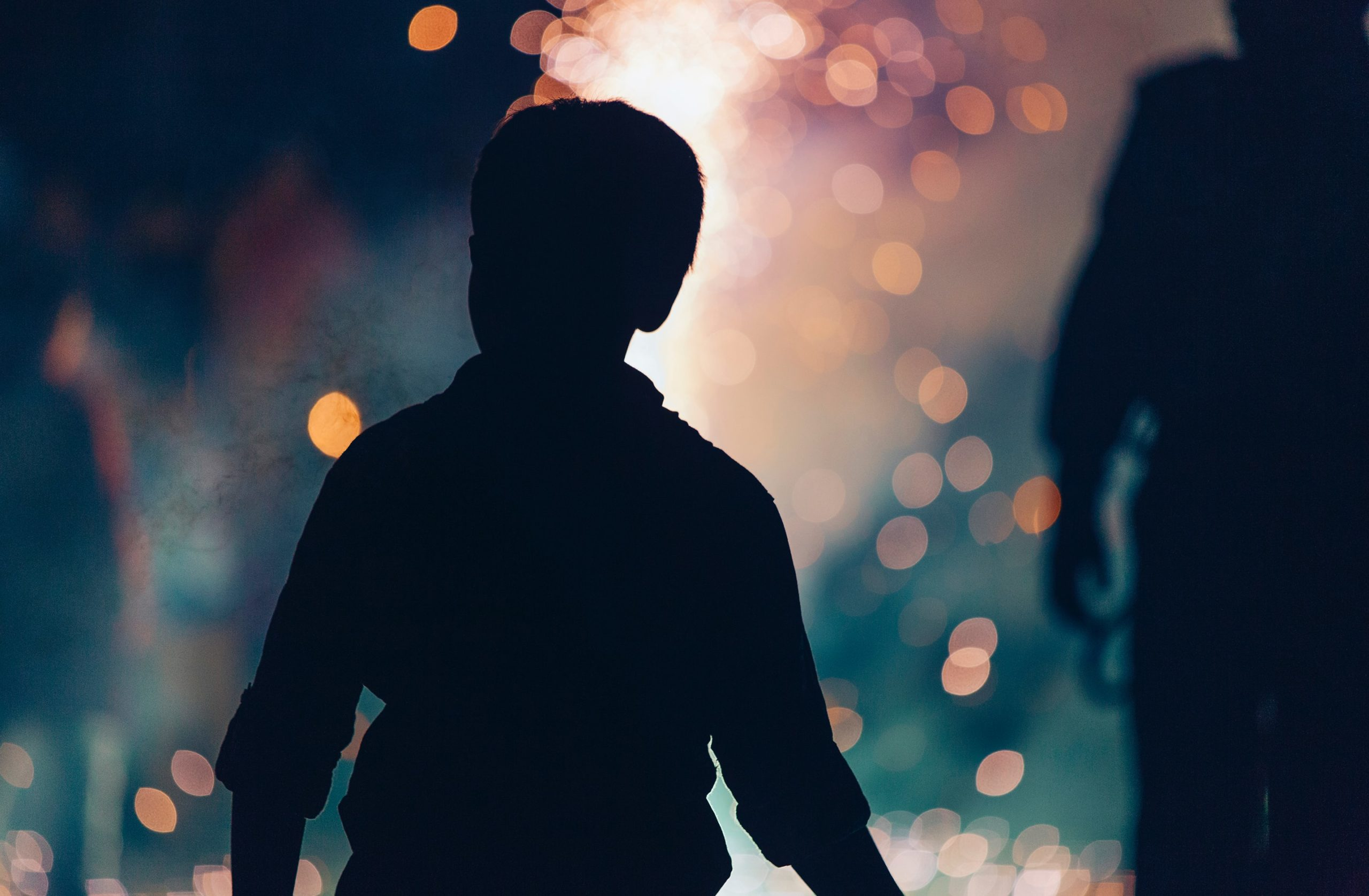 celebrations: a silhouette of a child in front of burry fireworks