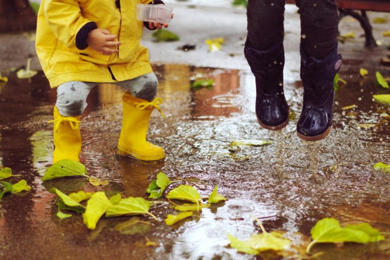 Playing outside: two children jumping in puddles with welly boots on