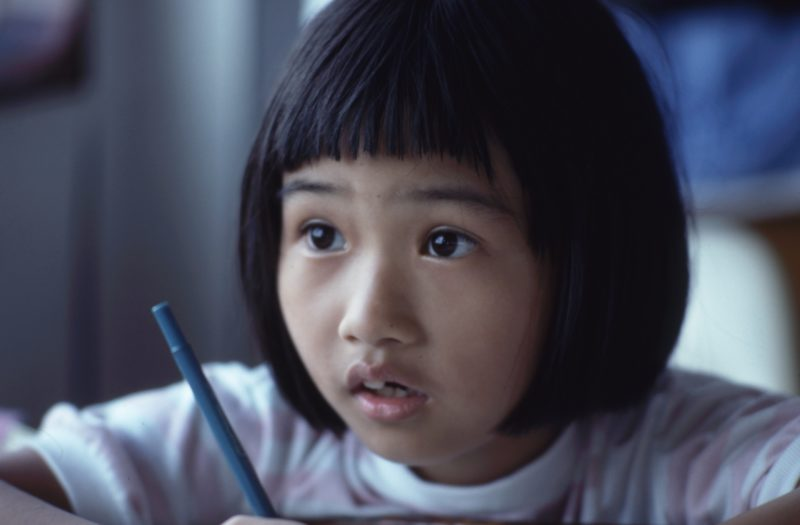executive function: a child looking up while holding a pencil