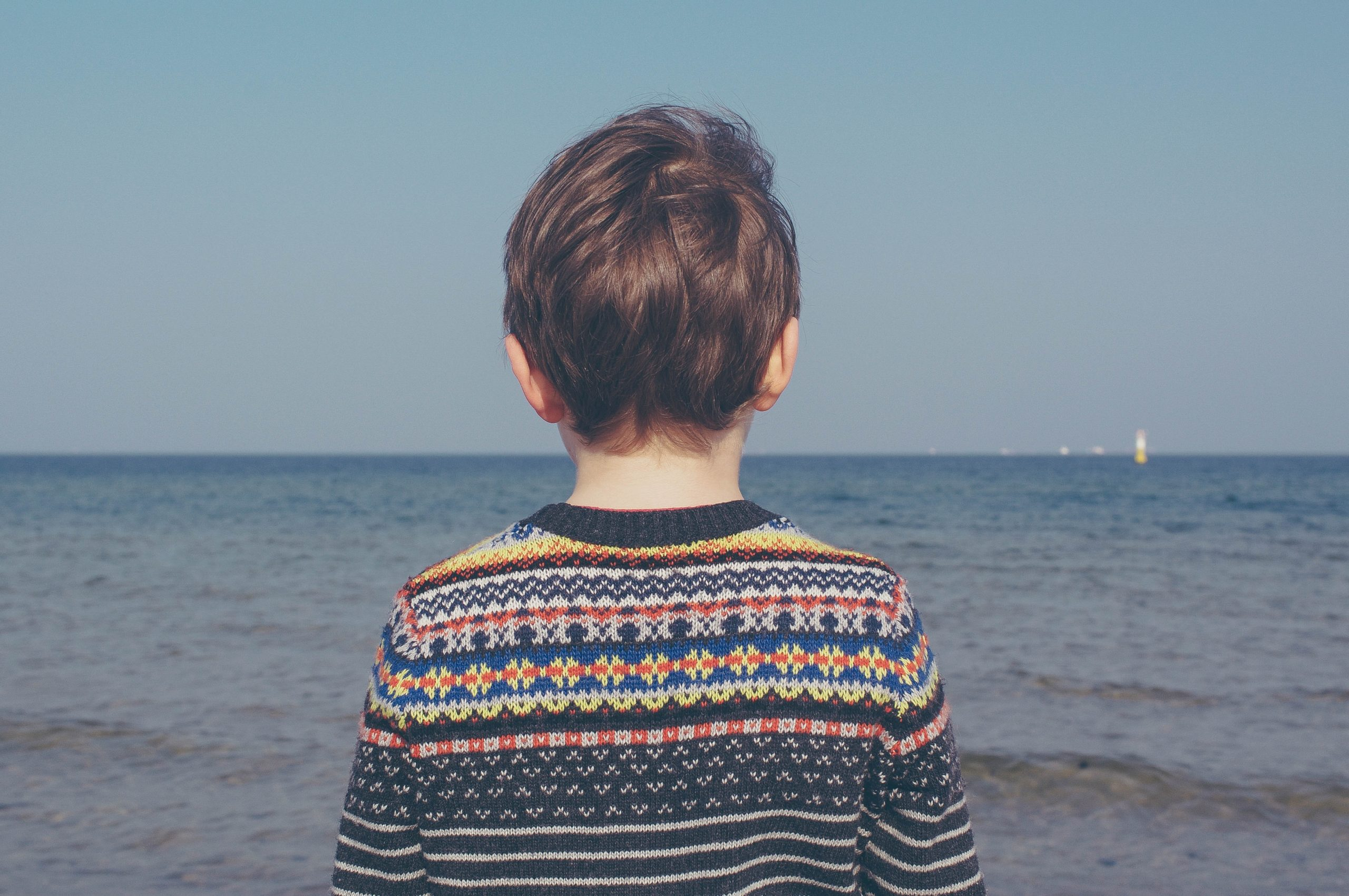 autism assessment: a young child looking at the sea, wearing a stripey jumper