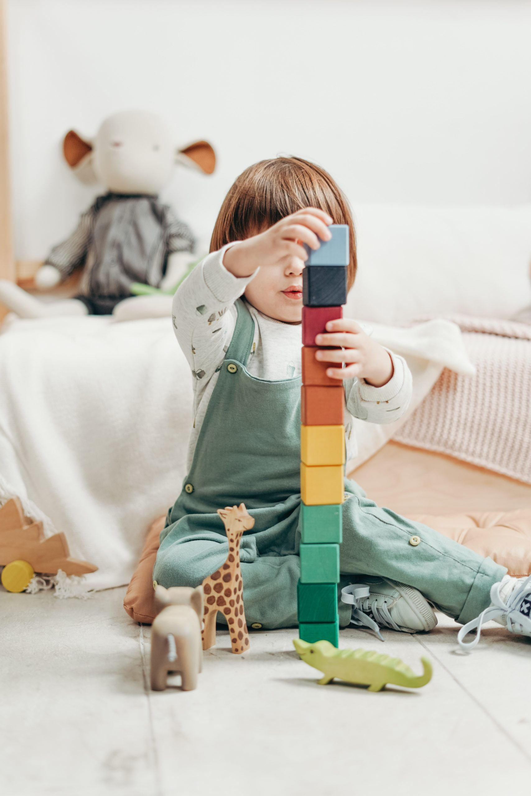 autism: a child wearing dungarees plays with coloured blocks