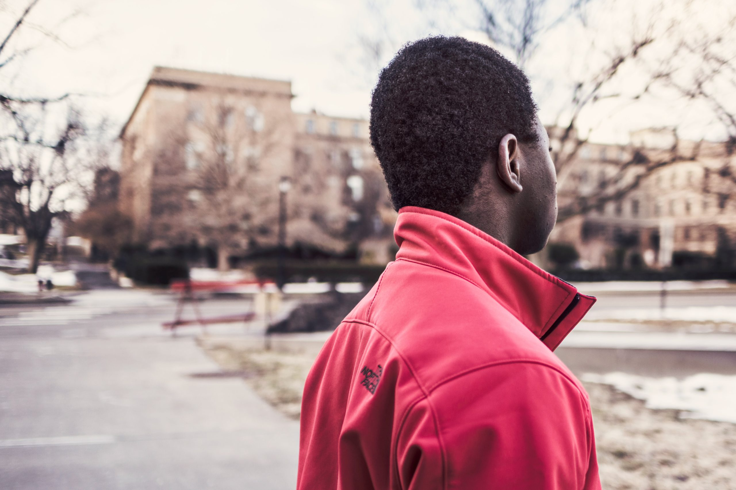 SEN safety: a young man looks into the distance wearing a red coat