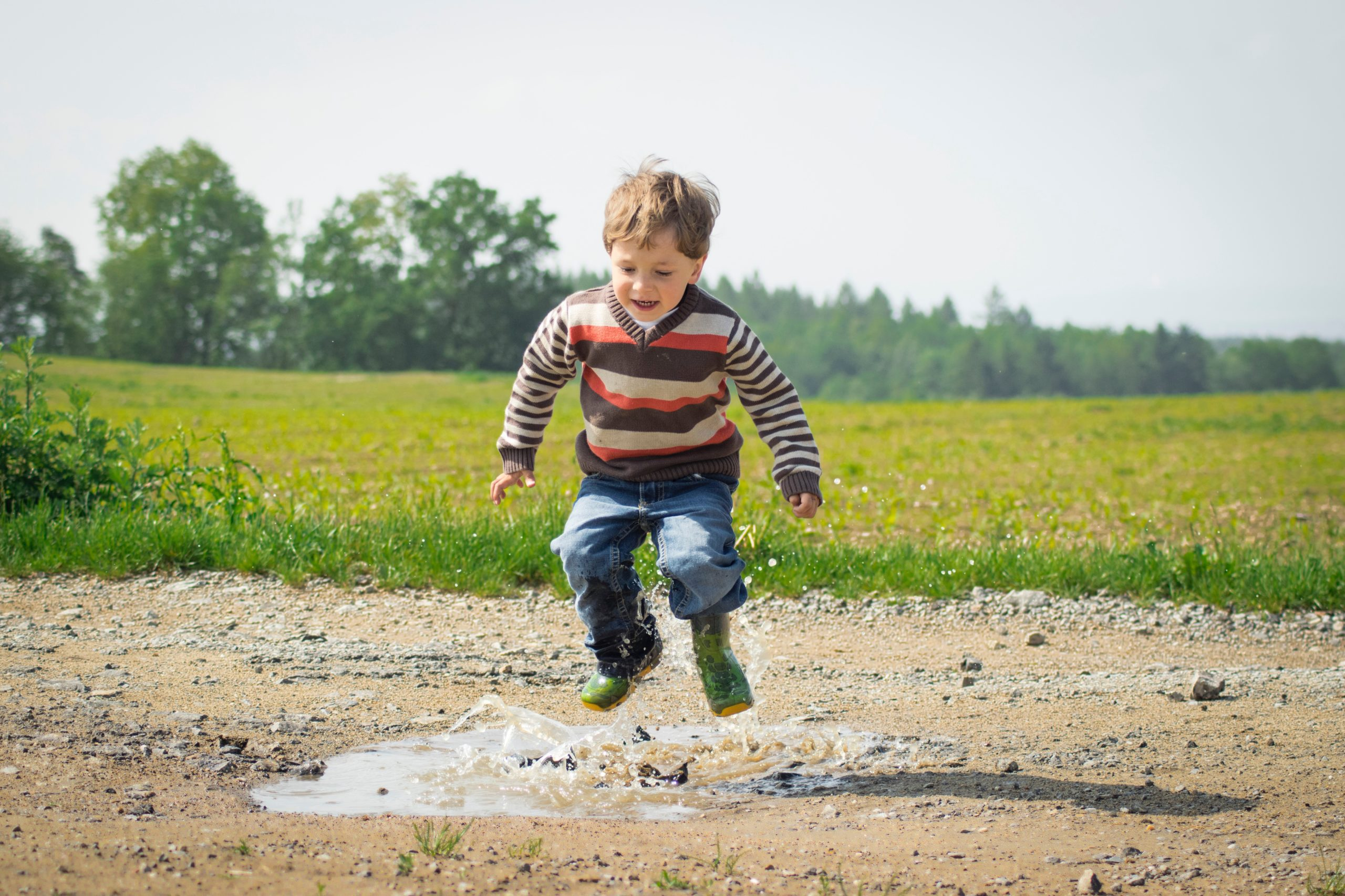 autism diagnosis: a child playing in a puddle in the middle of a green field