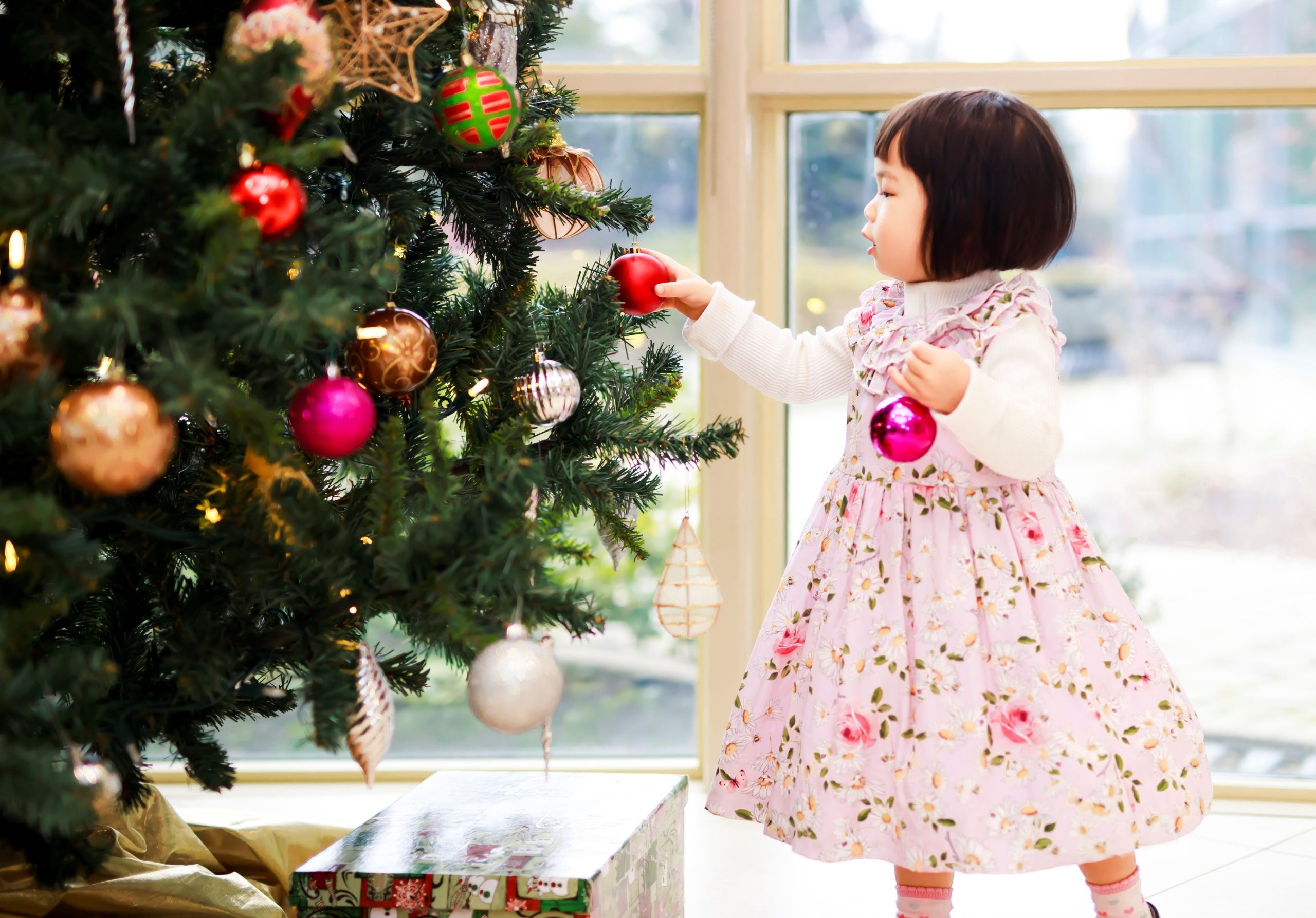 SEND at Christmas: a small child in a pink dress puts a red bauble onto a Christmas tree