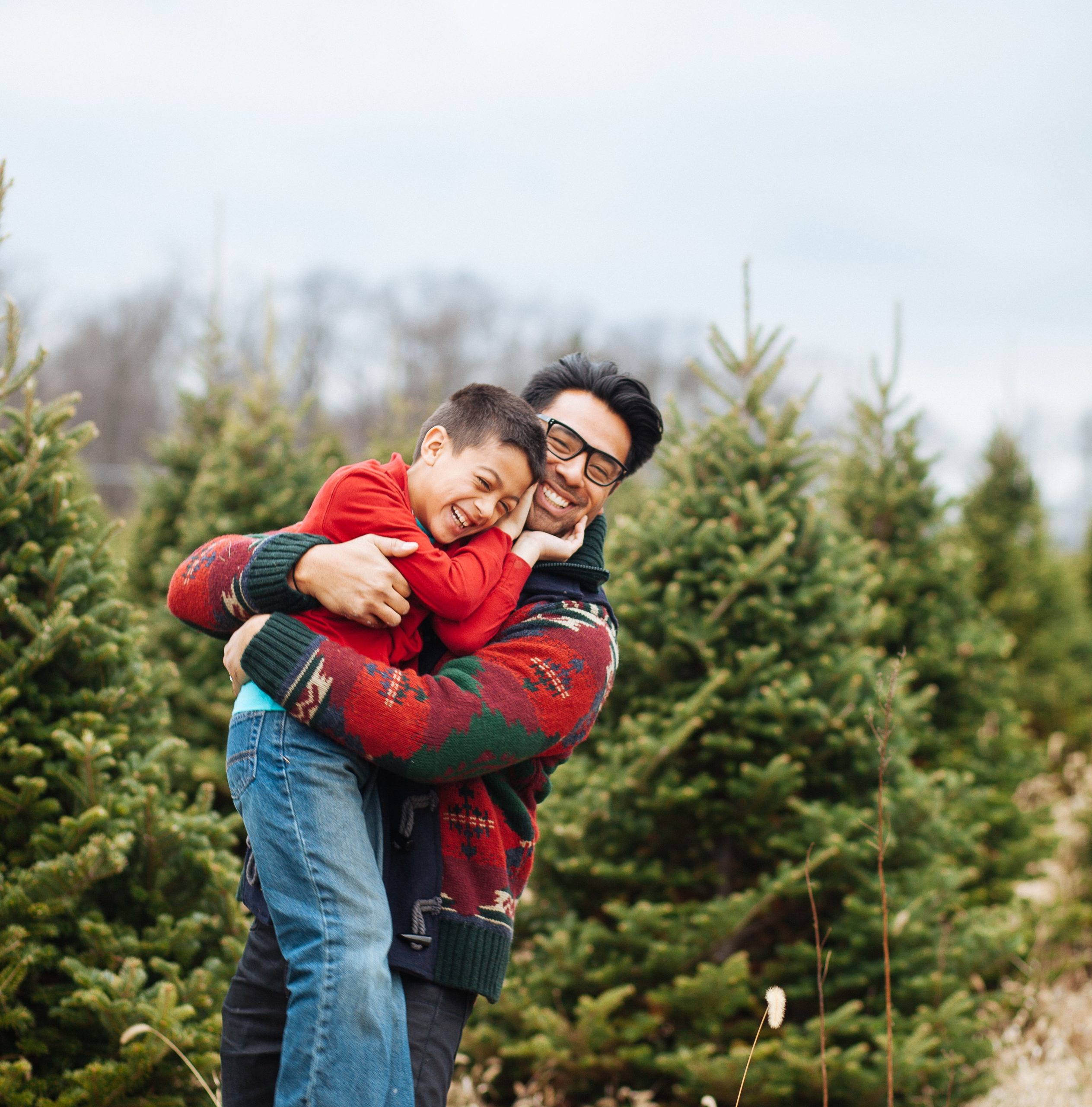 Co-parenting: a parent picking up a laughing child in front of a field of pine trees