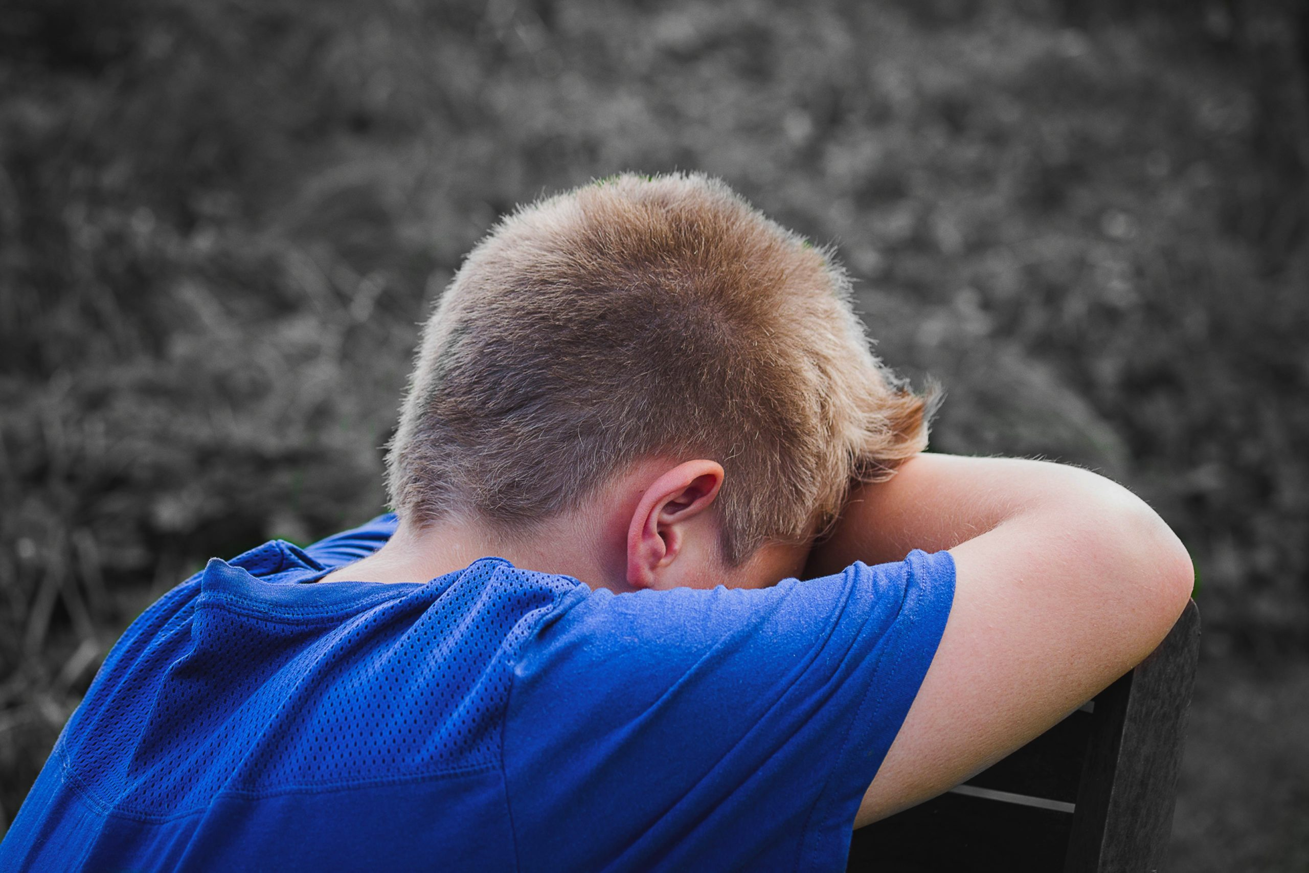 challenging behaviour: a child in a blue top hides their face with their hands