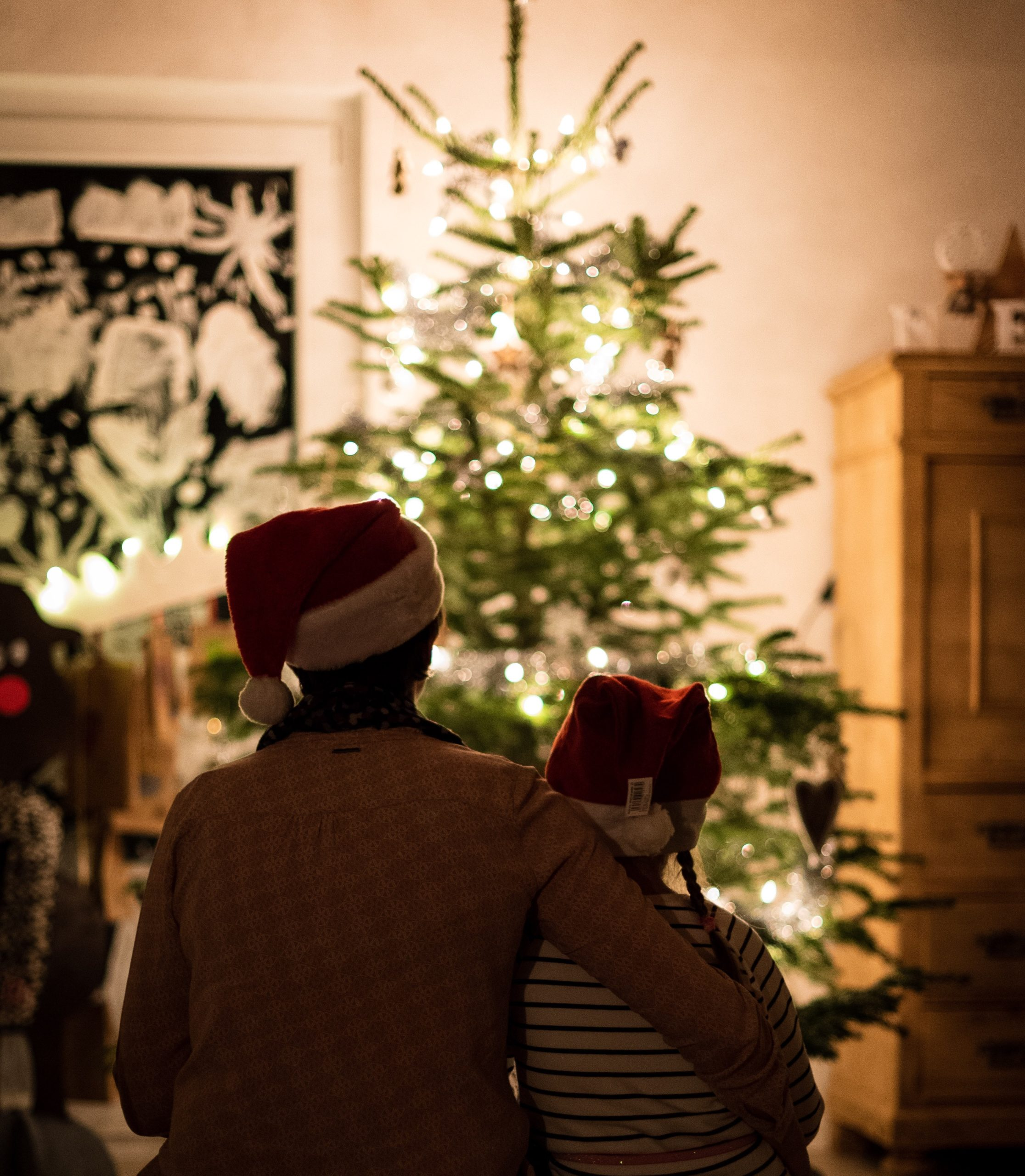 Christmas bubble: a parent and child in christmas hats in front of a christmas tree