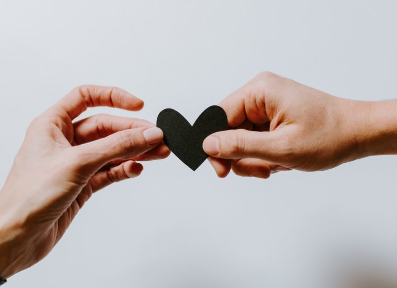 Healthy relationships - hands holding paper heart
