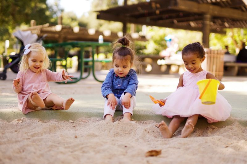 teaching kindness - young girls play together in a sandpit